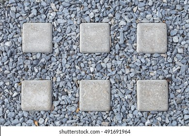 Pattern of concrete squares with stone pebbles in the walkway.
