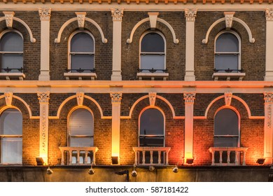 The pattern created by windows in a facade of a old victorian building in central london with bright colored lights in the botom