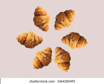 Pattern from croissants isolated on brown background. Bakery pattern with baked croissant. Fresh croissant with salad and grains pattern. Croissant cookies sprinkled with grains on a brown background