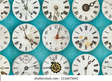Pattern of different antique weathered clocks on a wall