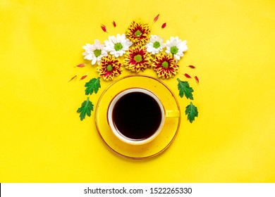 pattern of flowers of red and white asters, green leaves and a cup of hot coffee Americano on yellow background Flat lay Top view Mock up Sesonal concept Hello autumn, spring or summer, Good morning