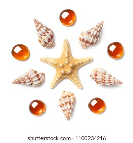 Pattern in the form of a circle made of shells, starfish and orange glass pebbles isolated on white background. Flat lay, top view. The concept of summer holidays and travel