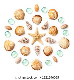 Pattern in the form of a circle made of shells, starfish and green glass beads isolated on white background. Flat lay, top view