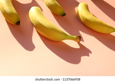 Pattern of fresh bananas on a bright, colorful pastel pink background.