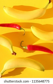 Pattern of fresh bananas and red chillies on a bright, colorful yellow background