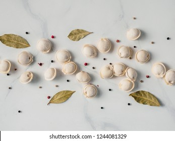 Pattern of frozen uncooked russian pelmeni with peppercorns and bay leaves on white marble table. Creative layout of dumplings. Beautiful scattered raw dumplings. Top view or flat lay.