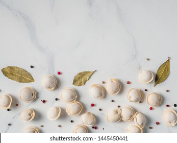 Pattern of frozen uncooked russian pelmeni with peppercorns and bay leaves on white marble table. Creative layout of dumplings. Beautiful scattered raw dumplings. Top view or flat lay. Copy space