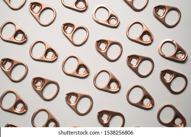 Pattern of gold metal ring pull or pull tab lid for bottle or can opener on white background , recycle and eco concept