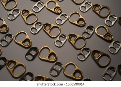 Pattern of gold and silver metal ring pull or pull tab lid for bottle or can opener on dark background , recycle and eco concept for background and texture