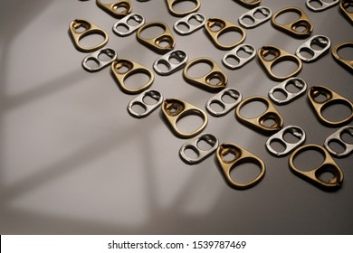 Pattern of gold and silver metal ring pull or pull tab lid for bottle or can opener on dark background , recycle and eco concept for background and texture with copy space