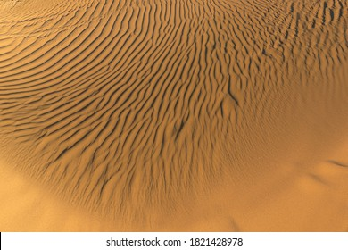Pattern of golden sand on a beach in the summer. The textured surface of sand on the beach after a strong wind in the form of waves close up. Ribbed sand texture. Yellow river sand background
