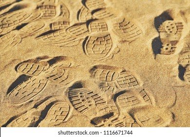 The pattern of golden sand with trampled footprints from boots on the beach in the summer. Footprints from the shoe protectors. Textured surface of sand on the beach close-up. Ribbed sand texture