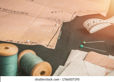 Pattern of graph paper on black fabric, two bobbins of thread,  white measuring tape and sewing pins. Workplace of a seamstress or tailor. Small business concept.