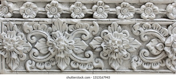 Pattern of gray flower carved on stucco design of native wall, Thai style in temple