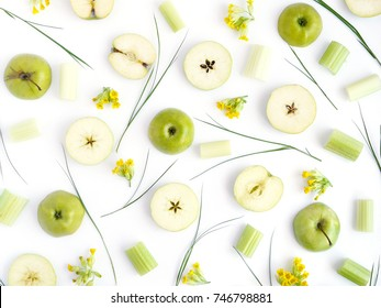 Pattern of green apples. Fruits and flowers on a white background. Wallpaper of fruits. Composition of sliced apples.Top view, flat lay.