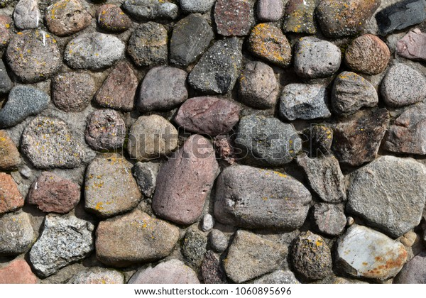 Pattern of grey decorative random sized stones outdoors wall with concrete connection as natural surface background.