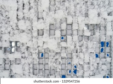 Pattern: Interesting view from below on a snowy metal grating at a lift station in Finland