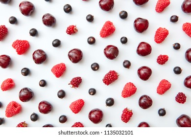Pattern of juicy ripe raspberries, currants and cherries on a white background. Summer concept. Flat lay