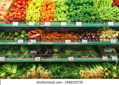 Pattern laid out organic vegetables, fruits and herbs on shelves at farmers marketin the city. Bright colors of healthy food broccoli, lettuce, eggplant, zucchini, onions, peppers, garlic, tomatoes