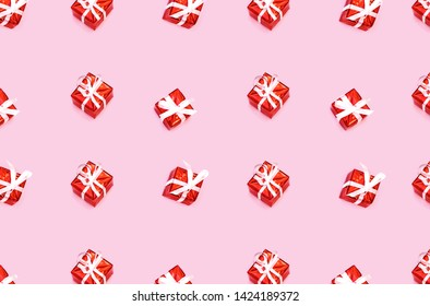 Pattern made from Christmas gift boxes isolated on pink backhround. Festive concept.