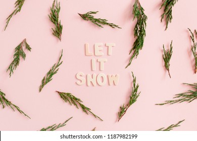 Pattern made of conifer tree branches on a pink pastel background. Quote made of wooden letters - Let it snow