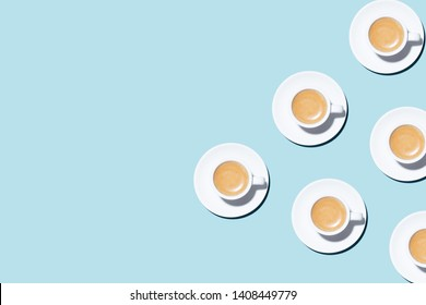 Pattern made of cup of cappuccino on blue background. Trendy minimal styled flat lay photography with cups of coffee.