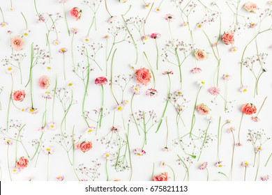 Pattern made of orange rose flowers, pink gypsophila flowers and daisy flowers on white background. Flat lay, top view