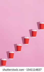 Pattern of many red paper coffee cups with white plastic covers laid in a row as a success ladder on pink backround. Flat lay. Morning, new day and ecology concept.
