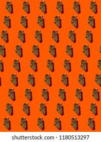 Pattern of marijuana buds on orange background.