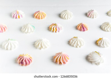 Pattern with meringues on a white wooden background. Multicolored meringues on a white background. Basis for confectionery banner, cafe, sweet shop. Meringue banner