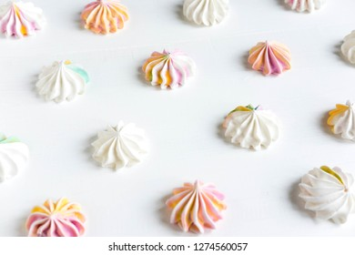 Pattern with meringues on a white wooden background. Multicolored meringues on a white background. Meringue banner