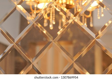 the pattern of mosaic square mirror tiles with chandelier reflected in them