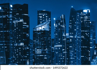 Pattern of office buildings windows illuminated at night. Lighting with Glass architecture facade design with reflection in urban city, Downtown Singapore City in financial district.