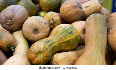 Pattern of pile of putternut pumpkins nutmeg lying chaotically scatterd. Pumkins nutmeg in vegetable market for sale