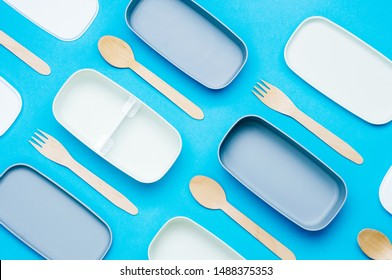 Pattern of plastic empty two-layered lunch boxes with wooden forks and spoons on blue background. Top view, flat lay.