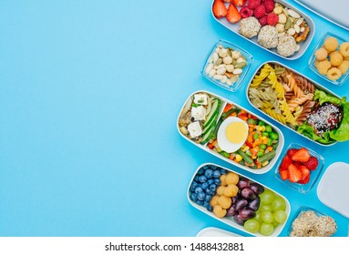 Pattern of plastic lunch boxes filled with healthy food, fresh fruits and berries on blue background with blank space for text. Top view, flat lay.