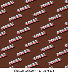 Pattern of red polka-dots clothespins on brown background.