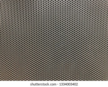 A pattern of regular perforations of metal