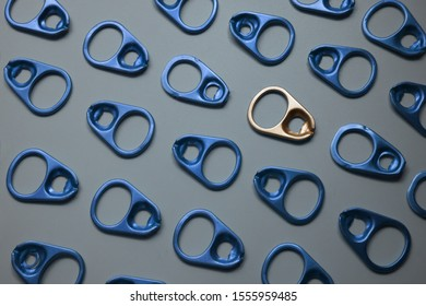 Pattern of ring pull or can pull tab ,one gold pull tab different from the rest in blue ,represent differentiation ,unique, outstanding ,independent and individually concept ,in grey background