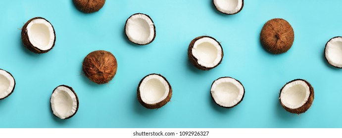 Pattern with ripe coconuts on blue background. Top View. Copy Space. Pop art design, creative summer concept. Banner. Half of coconut in minimal flat lay style