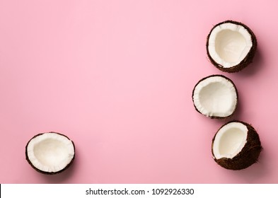 Pattern with ripe coconuts on pink background. Top View. Copy Space. Pop art design, creative summer concept. Banner. Half of coconut in minimal flat lay style