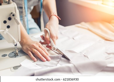 pattern, scissors, tape measure, and a sewing machine. Workplace of seamstress. Dressmaker cuts dress detail on the sketch lines.