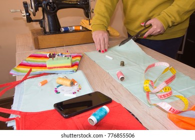 pattern, scissors, tape measure, and a sewing machine. Workplace of seamstress. Dressmaker cuts dress detail on the sketch lines. Garment industry, tailoring concept