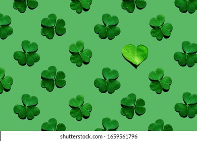 Pattern of shamrock leaves and one heart-shaped leaf on green background. St. Patrick's Day, selective focus.