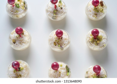 a pattern of a small beautiful  elegant middle eastern desserts, malby, coconut, pistachios, raspberries sauce