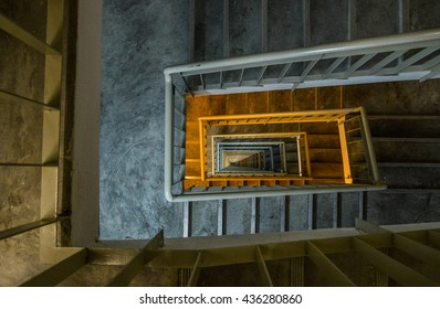 pattern of the spiral of staircases in skyscraper building in low light