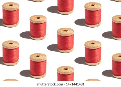 Pattern of spool of red thread on a white background