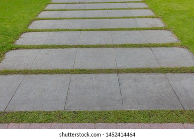 Pattern of square cement floor tiles with green grass blackground