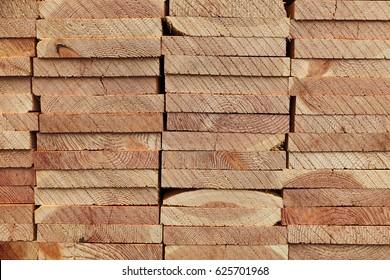 Pattern of stacked rectangular wooden beam timber at sawmill lumberyard