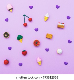 pattern of sweets: ice cream, cake, cupcakes, donuts, cakes and hearts on a purple background.